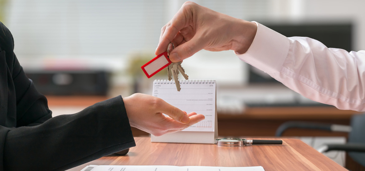 Real estate concept. Realtor is passing keys to the client sitting behind desk with contract